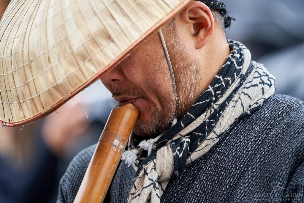 Japanese man playing a bamboo Pipe